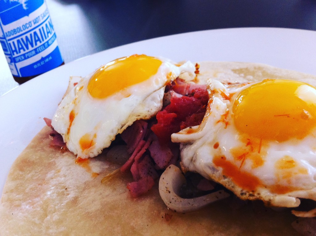 Breakfast Taco with Ham, Onions and Sunnyside up Eggs in a grilled soft tortilla slathered in Adoboloco Hawaiian Chili Pepper Water